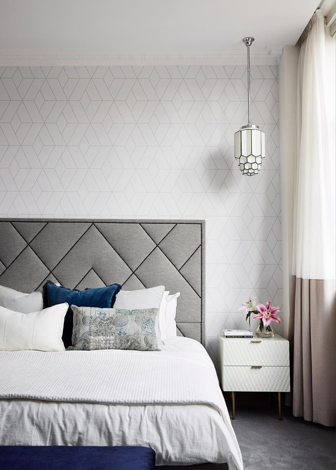 Good-quality bed linen, flowers in a vase and an opulent pendant light create an upmarket space.