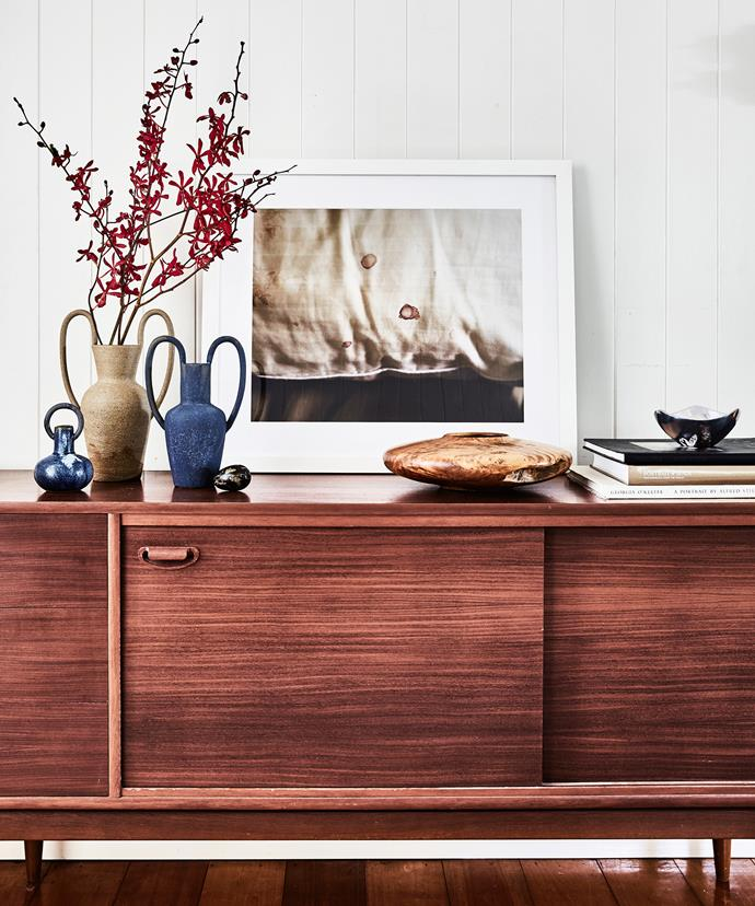 """The sideboard I found at Vinnies for just over $100 – I like that it adds a touch of mid-century style to the room. The vases and photograph are by Nicolette and the silver bowl is from Nambe."
