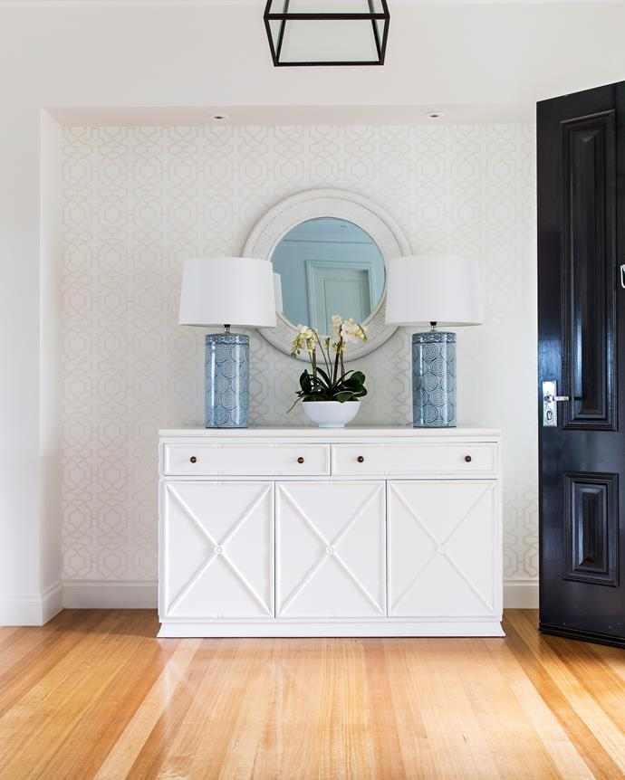 Stunning lamps and Thibaut wallpaper set the tone of classic style from the get-go.