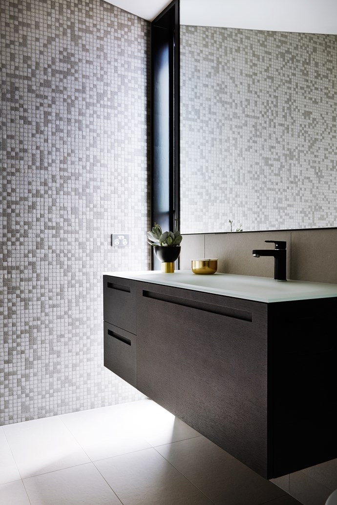 The dark-toned vanity seems to be suspended in midair, while the pixellated patterning of glass mosaic wall tiles suggests movement.