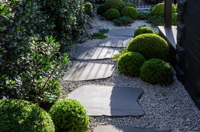 Random cut bluestone flagging surrounded by gravel weaves from the front gate to the home's entry.