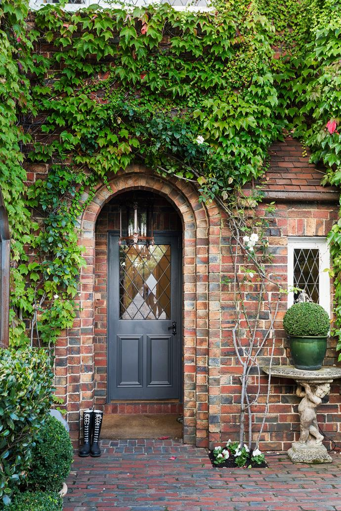 Ivy and climbing roses, underplanted with pansies, play up the old-world charm of this manor-style home.