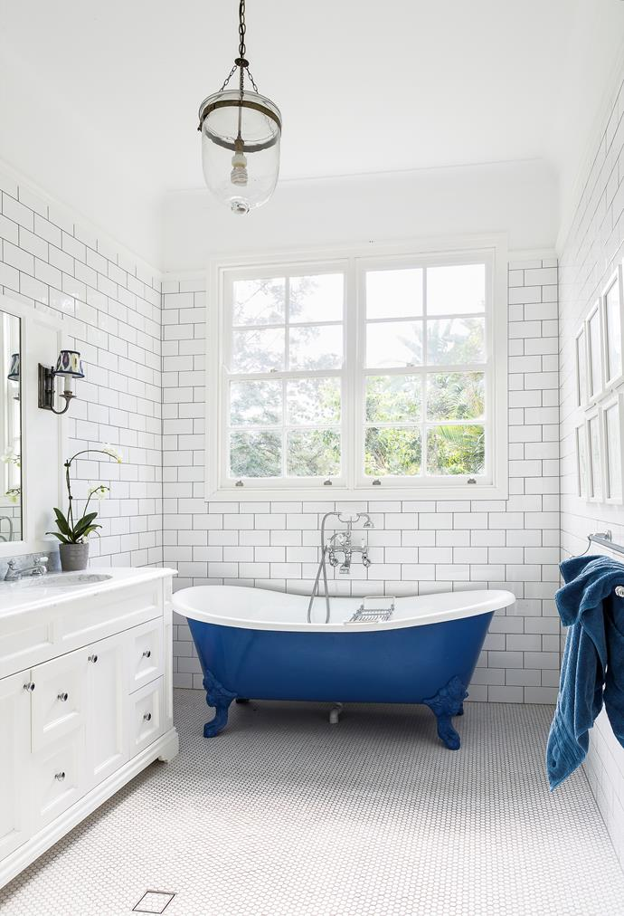 The blue bath takes centre stage. Outside, blue and white agapanthus frame the property. Bath and tiles, Black & Spiro. Tapware, from Perrin & Rowe.