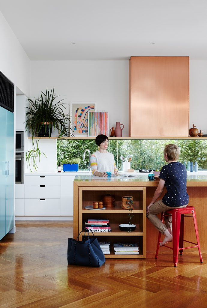 Instead of a standard splashback, the family opted for a long window looking to the leafy side return. Entry to a butler's pantry is at left. The island is Victorian ash; the rear bench is Corian in Glacier White. Copper-clad rangehood by TCM Building Group.