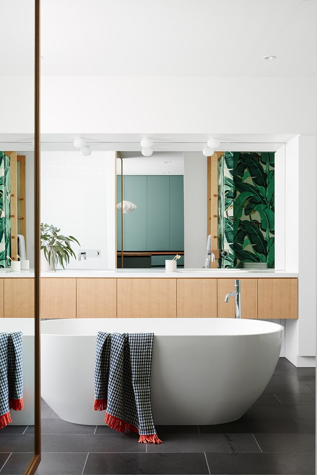 "For the most part, this bathroom, in a [modernist Melbourne home](https://www.homestolove.com.au/renovated-modernist-melbourne-home-5581|target=""_blank"") has been kept simple and elegant with neutral cabinetry, Bluestone floor tiles and a white freestanding bath. But take a peek in the mirror and you'll see a pop of zing from the leaf-patterned feature wallpaper. *Photo: Annette O'Brien / Story: Australian House & Garden*"