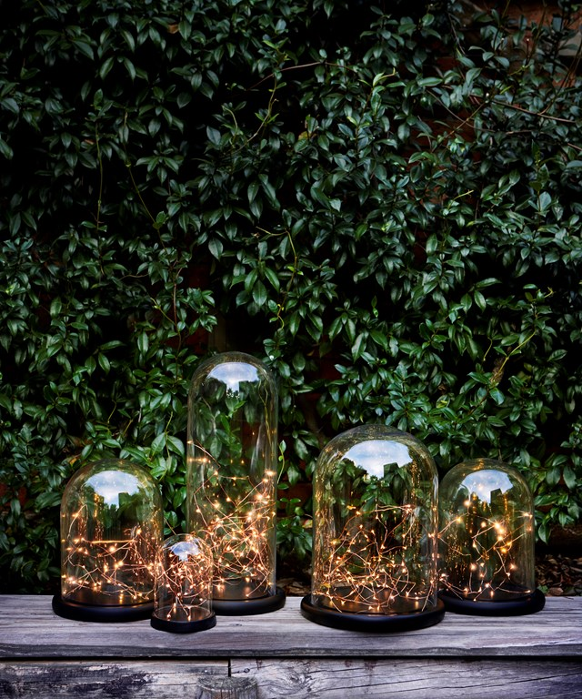 Fairy lights inside a decorative glass cloche creates an illuminating table centrepiece.