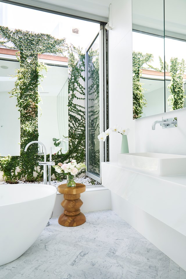 "Designed by the homeowner herself, this stunning [ensuite bathroom](https://www.homestolove.com.au/a-white-bathroom-with-its-own-courtyard-5622|target=""_blank"") overlooks a quaint, mirrored courtyard garden. Creating a space with a strong indoor-outdoor connection was important for the owner, who chose deliberately understated materials to allow the lush greenery to take centre stage. *Photo: John Paul Urizar / Styling: Sarah Maloney / Story: Australian House & Garden*"