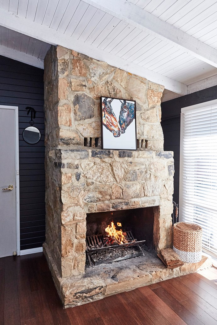 In the fireplace room, the sandstone was lost against the white, so we painted the walls in the same dark charcoal to create contrast. It was the best decision we made.