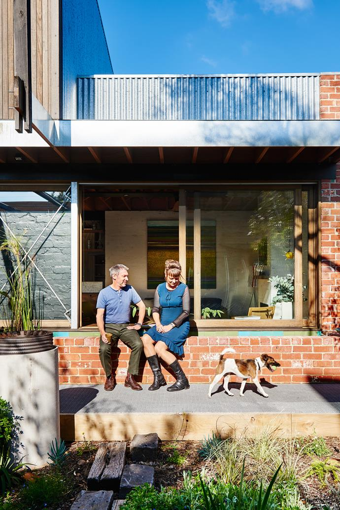 Architect-owners Tony Stuart and Polly Bastow with fox terrier Rosie. To the left of the window is their heat-generating Trombe wall, with brickwork painted Dulux Black Ace. The deck is made from Envirowalk 'Micro Mesh' grating, a fibreglass product often used in parks.