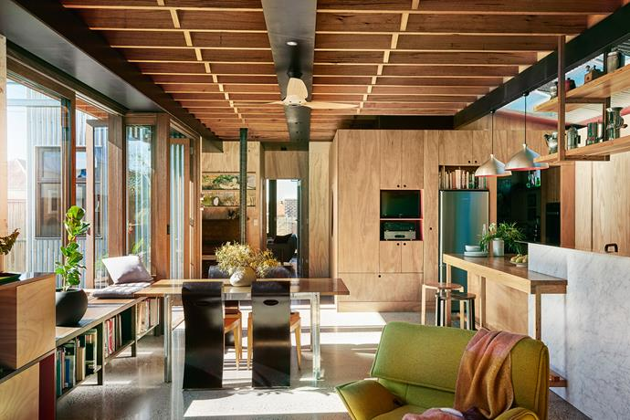 The internal 'pod' structure contains a butler's pantry and laundry. Dining setting by Form Architecture Furniture. The walls are plywood while the kitchen benchtop and overhead shelf are made from recycled timber.