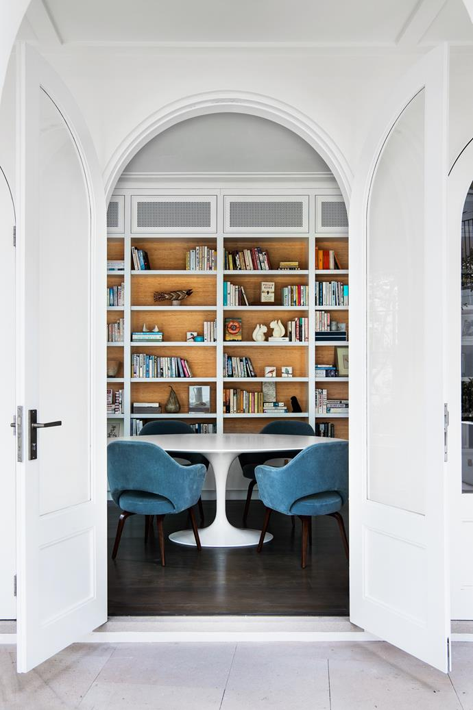 The library is framed through the recurring arch motif. Seagrass wallpaper and Saarinen table and chairs add a modernist note.