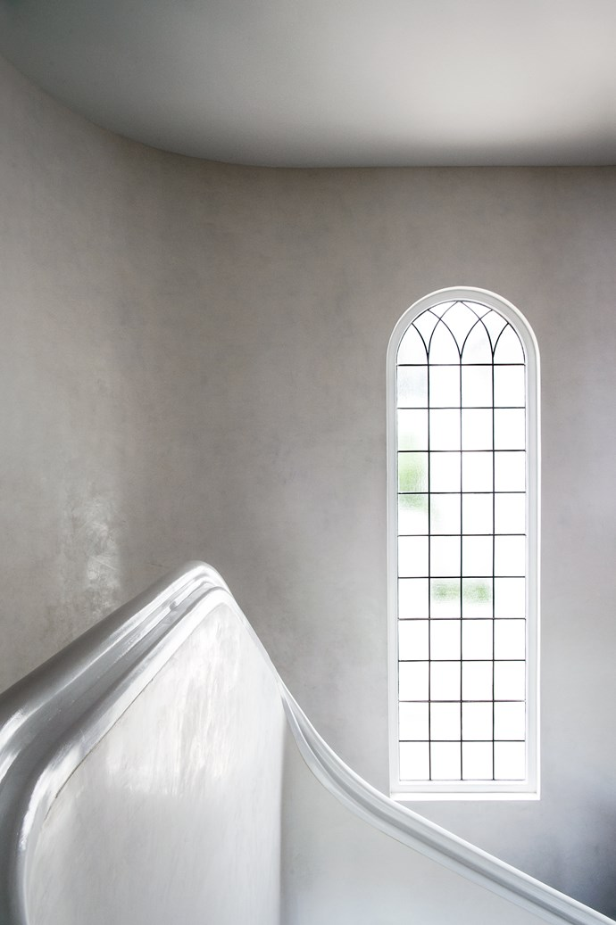 A multi-paned arched window illuminates the stair.
