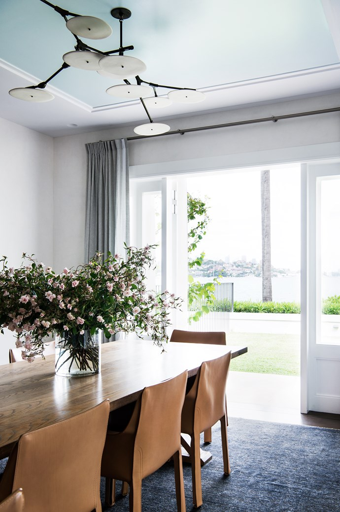 Cassina 'Cab' chairs surround the dining table. 'Branching Disc' light fitting by Lindsey Adelman.