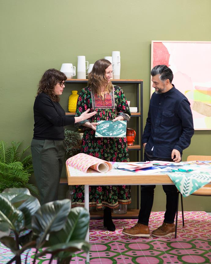 **1PM, BONNIE AND NEIL HQ** Bonnie unveils a new line of porcelain wall tiles to Dara Shashoua, owner of Byzantine Design, who will be retailing the tile range, and Claudio Oyarce, co-founder of the Denfair trade fair. At left, Bonnie holds a sample of the 'Banksia Wreath' tile. A corner of the studio (far left) is invitingly styled with cushions from the Forest collection and a floral oil painting on timber by Bonnie.