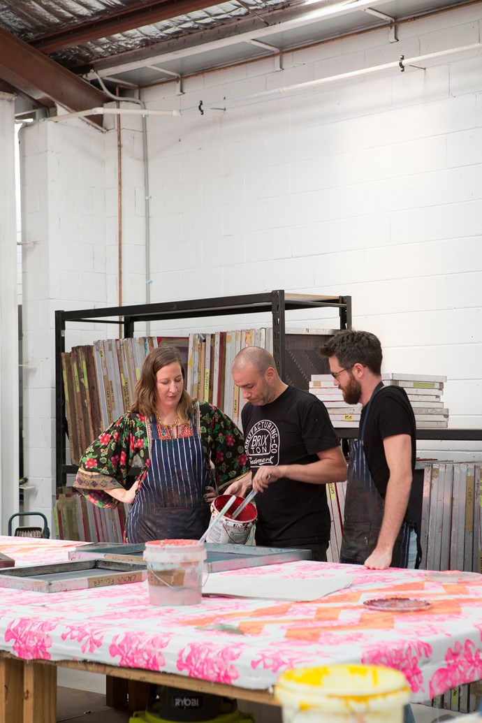 """**3PM, SCREEN-PRINTING ROOM** """"Neil does a lot of the printing and is super-fast. He's amazing,"""" says Bonnie, seen here at the print table with Neil and screen-printer Luke Mangelsdorf as they work on tea towels. Bonnie and Neil currently employ five full-time staff and a few part-timers. """"The team cares about the details as much as Neil and I do,"""" says Bonnie. """"The guys take great pride in making sure the flowers are placed in the right spot and everything is printed perfectly."""""""