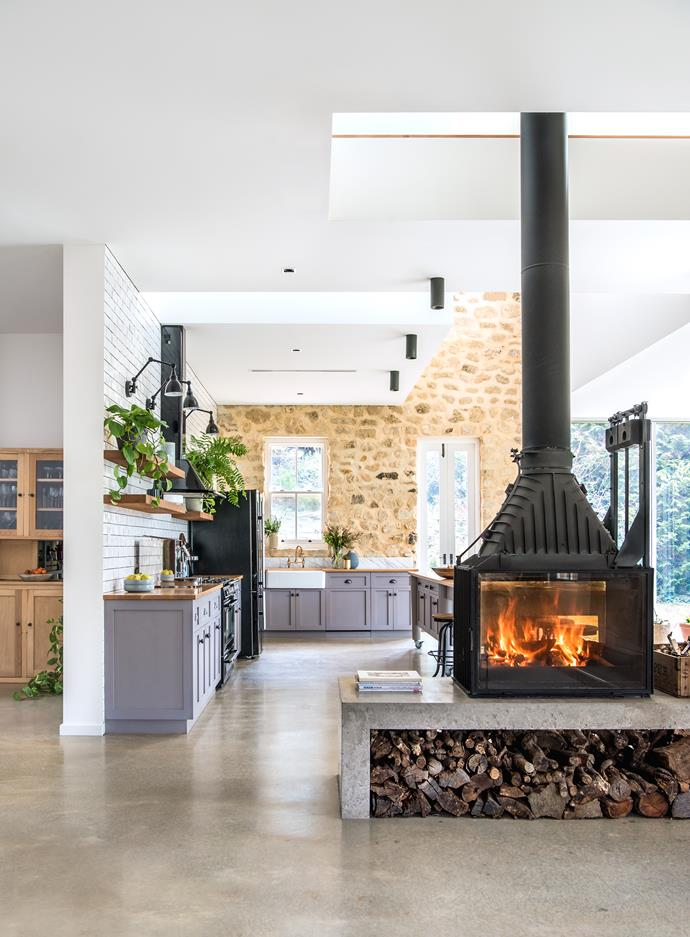 A Radiante 846 2V double- sided fireplace from Cheminées Philippe warms the living and kitchen areas; the neatly stacked woodpile adds a rustic note.