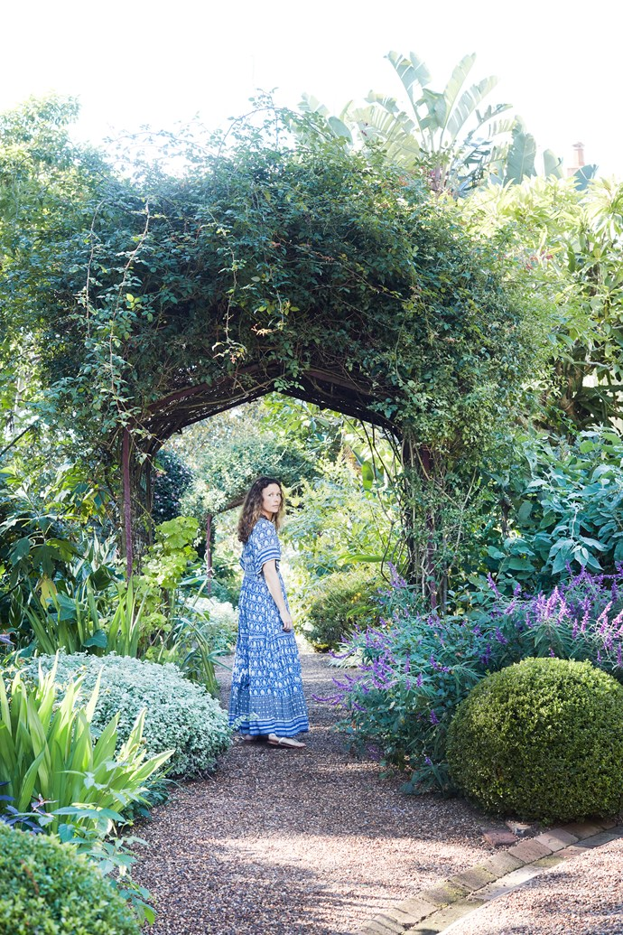 Anna walks through a bower surrounded by trees and plants tended by the van der Gardners, with regular help from Pepo Botanic Design.