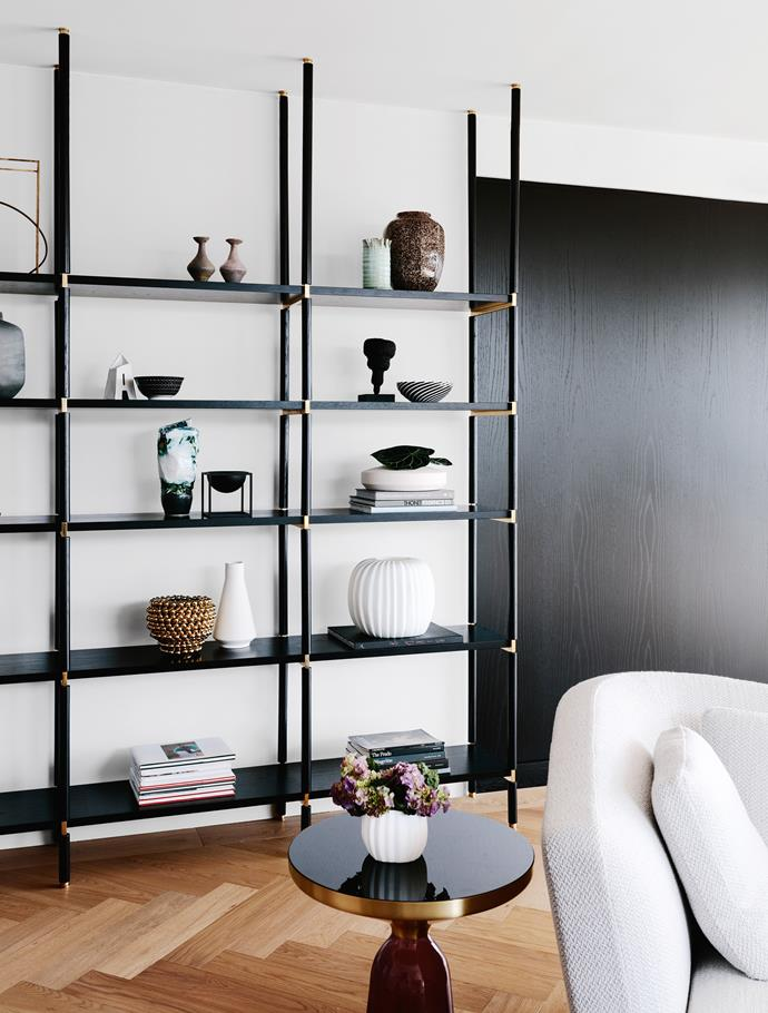Custom shelving in black stained oak and brass in the living room.