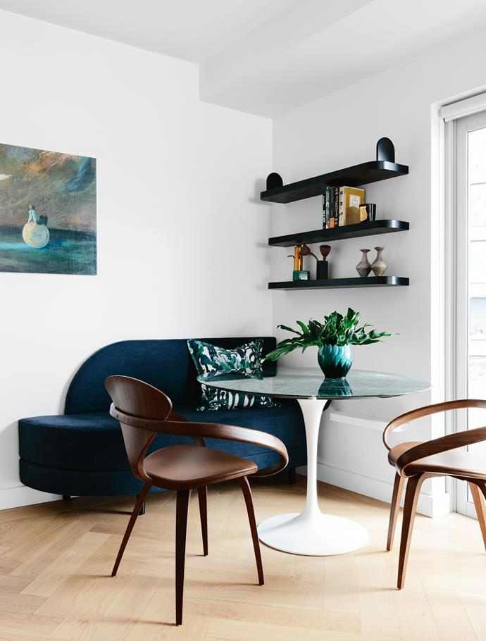 The dining nook has custom-designed shelves and a bench seat upholstered in navy linen. Eero Saarinen table with marble top and walnut Cherner chairs, all from De De Ce. Cushion is covered in Hermès silk.