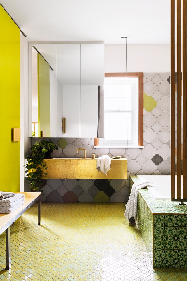 """An inset bathtub installed perpendicular to a statement vanity increases the spaciousness of this bathroom ten-fold. We also can't get enough of the clashing, yet cohesive, patterned tiles used throughout this [vibrant Melbourne home](https://www.homestolove.com.au/vibrant-home-interior-in-melbourne-by-multiplicity-5756