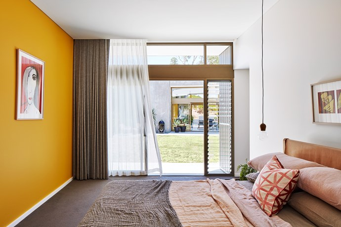 Bold red and yellow features warm up the grey base palette in the main bedroom.