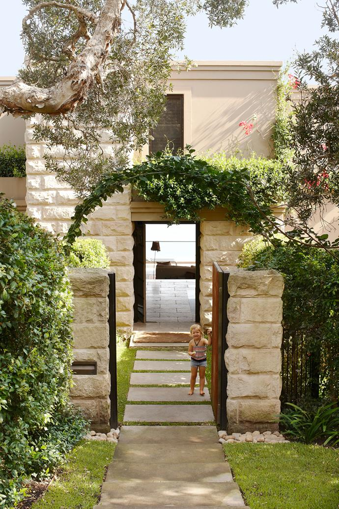 "At this front entry, created by Paul Bangay, boundary lines disappear, thanks to lilly pilly hedges and an arch of bougainvillea. ""Creepers spilling over walls or vines dripping from steel arches help to soften the entrance and welcome the visitor,"" says Paul. [paulbangay.com](http://www.paulbangay.com/