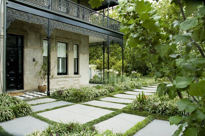 "Designed as a ""grassy, flowering meadow"", this garden visually anchors the grand home it surrounds, says Myles. The 'meadow' consists of purple and white Liriope, and mondo grass, plus clivia and liliums for seasonal colour. Paths of huge slate flagstones and tall tulip trees complement the scale of the home. [e-ga.com.au](http://e-ga.com.au/