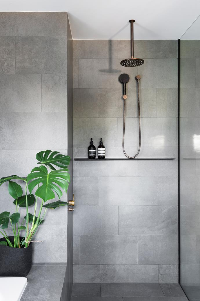 For continuity, the same concrete-look tiles and walnut veneer are used in both the home's bathrooms and kitchen.
