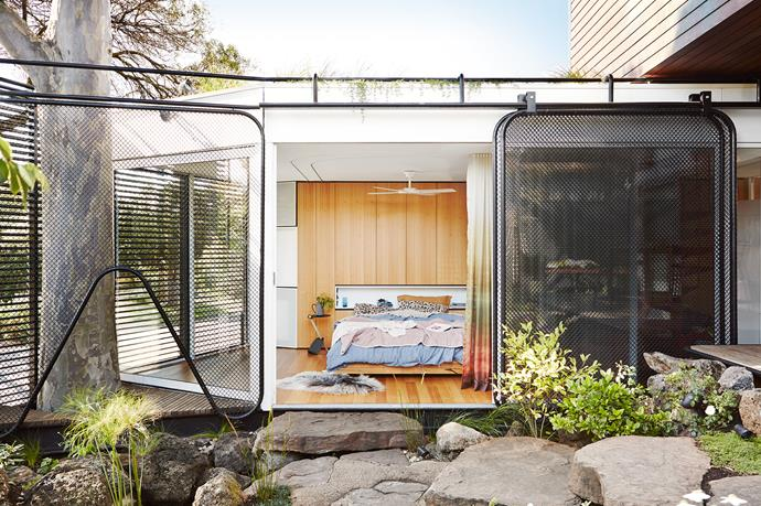This new section is accessed from a cupboard-like door in the kitchen, via the ensuite and office staircase. Its side window is protected by aluminium louvres and double-glazed sliding doors, while chain-link mesh doors on the garden side guard against dropping branches from the large gum tree.