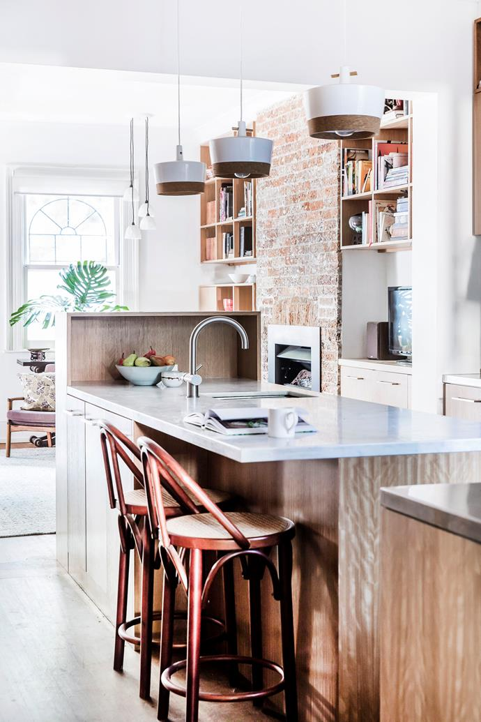 Sleek brushed stainless steel and marble balance the exposed brick hearth wall and plywood.