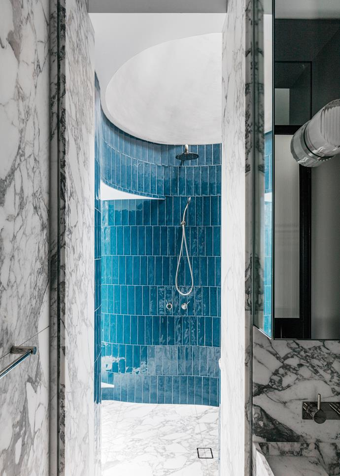 'Denim' tiles from Surface Gallery are laid vertically in the circular shower. Vanity is in Arabescato marble.