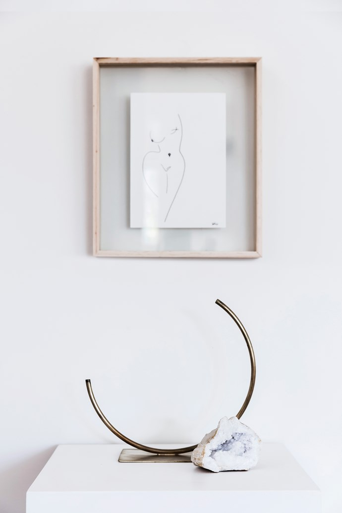 An ACV Studio brass vase by sculptor Anna Varendorff sits below a picture by artist Kat Bak.