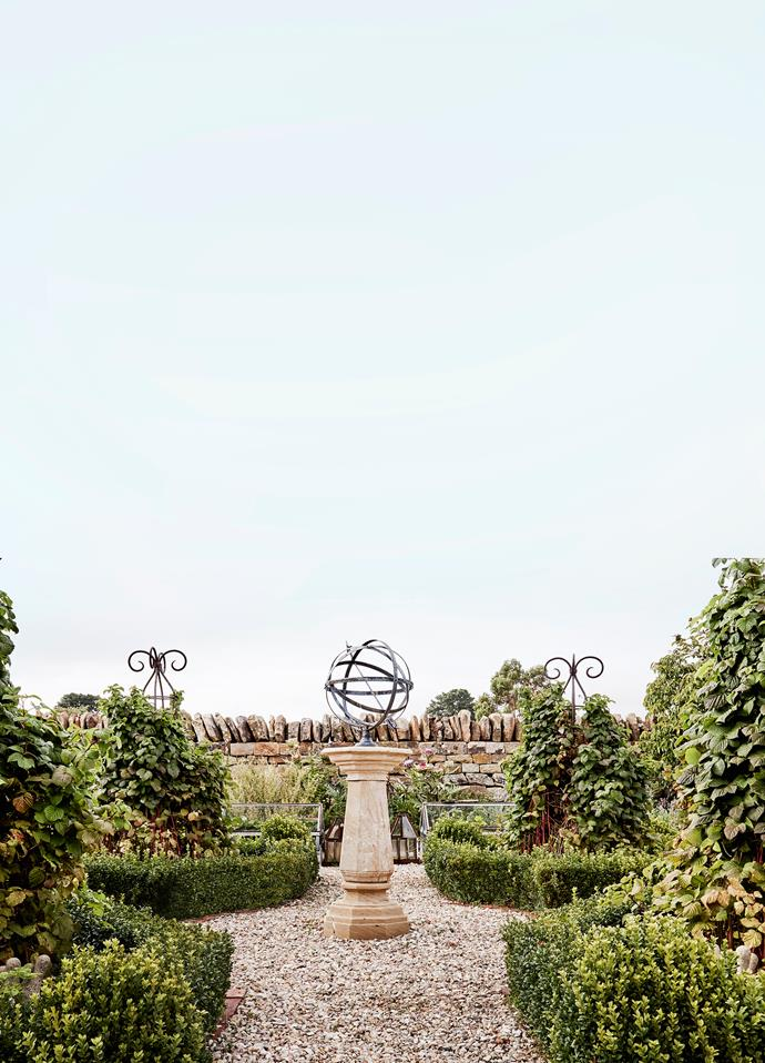 "The wall around this parterre garden was built by Cameron using local 'paddock rock'. At the centre, an armillary sphere sits atop an octagonal sandstone sundial, both from Provincial Antiques. To the sides, obelisks covered in thornless raspberries are encircled by English box hedge. ""The raspberry bushes are prolific,"" says Debbie. ""I used to make raspberry cordials with them, which our boys sold under the banner of Wilson Brothers Cordials at the farmers' market."""