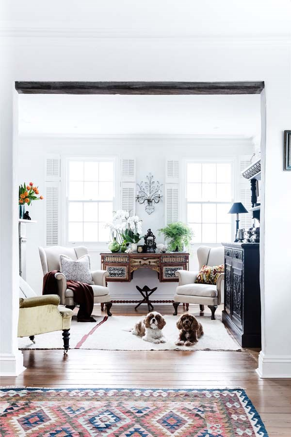 The South African stool belonged to the parents of owner Seamus Dinnigan. His cavalier King Charles spaniels, Dickie and Douglas, make themselves comfortable in front of vintage Parker Knoll armchairs from Lunatiques.   Sideboard, Tarlo & Graham. Decorative wall sconce, Elements I Love. Rug, Perryman Carpets. Throw, Planet. Cushion (left), Busatti.