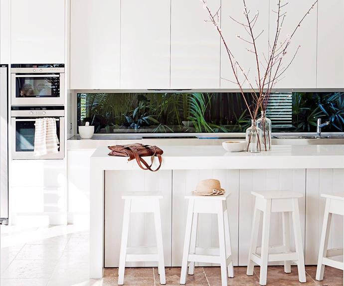 The white and bright interior of this kitchen is the perfect forefront to the [moody, lush garden](https://www.homestolove.com.au/splashback-ideas-for-kitchens-5481) seen through the splashback. <br><br>  *Photographer: Bauer Syndication / Homes+*