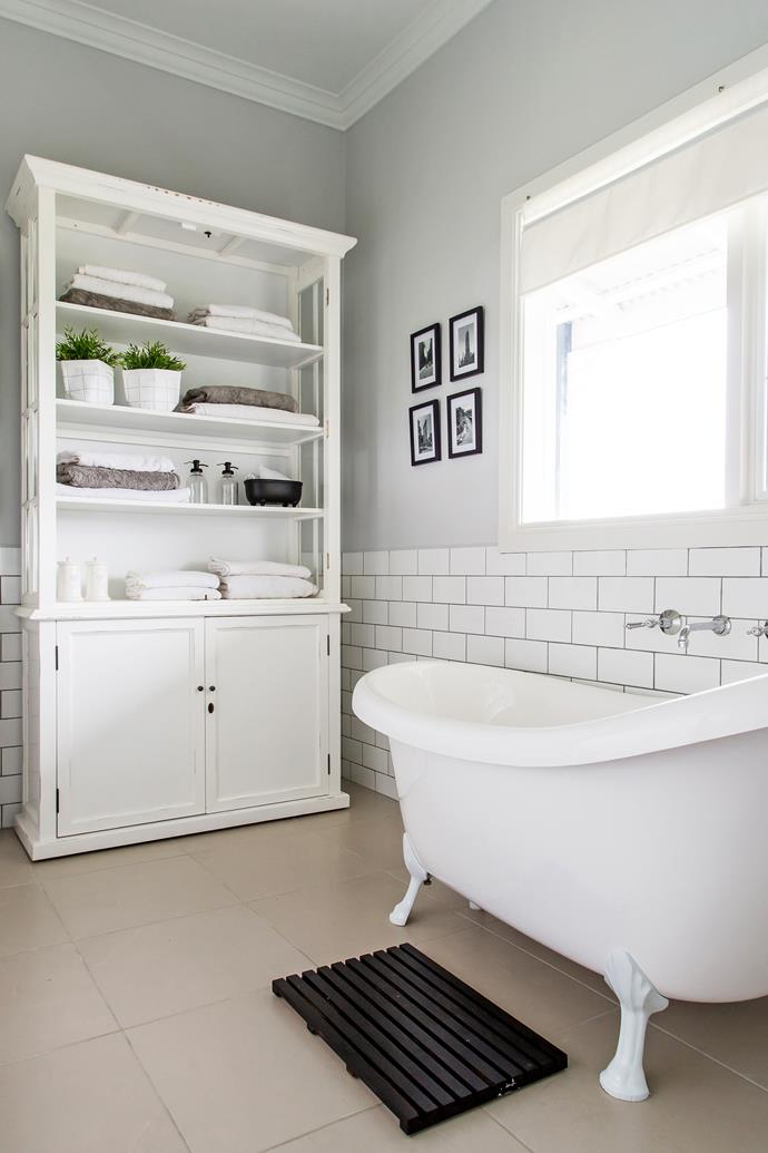 The claw foot bath from an Early Settler sale is an elegant feature of the main bathroom. Alicia removed damaged doors from this cupboard to create unique storage for towels.