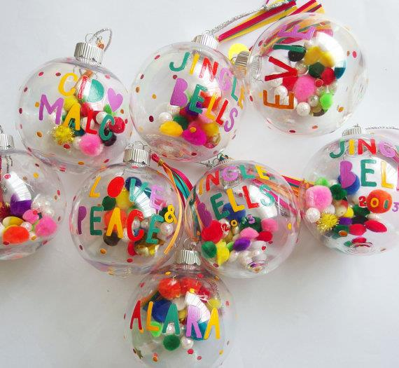 """This time of year is all about making memories. What better way to get the whole family involved than to hang personalised, hand-painted baubles on the tree? These ones are filled with multi-coloured pompoms. <br><br> Personalised, hand-painted Christmas baubles available from [Etsy](https://www.etsy.com/au/listing/167628366/personalised-christmas-bauble-colourful?ga_order=most_relevant&ga_search_type=all&ga_view_type=gallery&ga_search_query=christmas&ref=sr_gallery_13