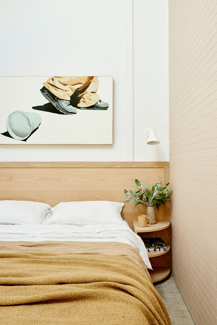 For additional storage, the custom-made bed also features drawers underneath. The unusual tiled feature wall creates a link to the other rooms. Inax 'Plain 50' tiles, from Artedomus. Custom bedside tables. Artwork by ELK Stencils.