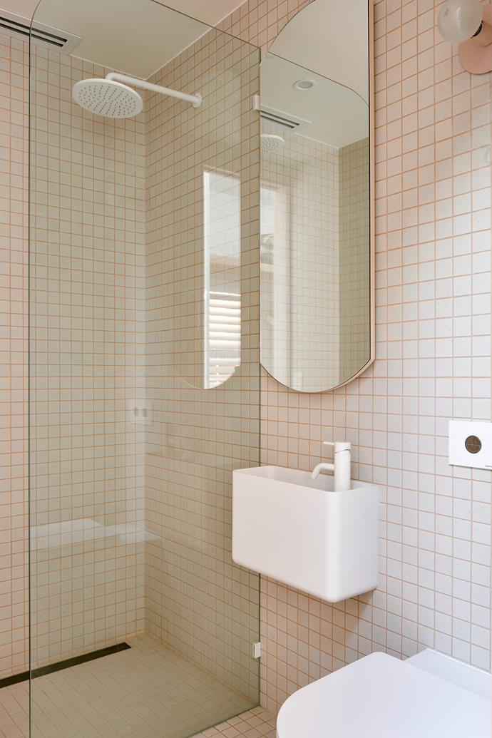 Josh and Jenna opted for white tiles with apricot grout in the bathroom, a subtle and interesting visual shift from the apricot tiles with white grout used elsewhere. Inax 'Sugie' tiles, from Artedomus. The custom-designed mirror cleverly conceals a storage niche.