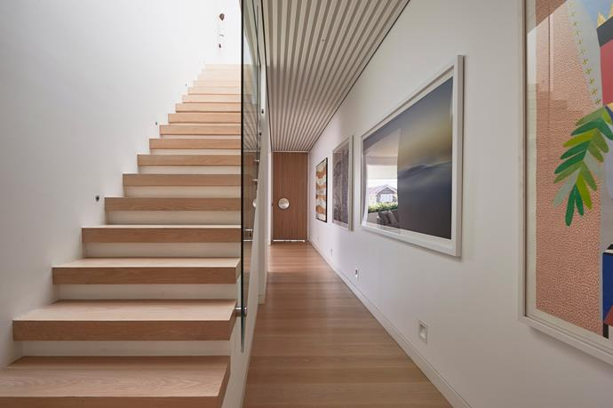 Clean lines and contemporary art line the hallway, while a timber staircase leads you upstairs to three bedrooms.