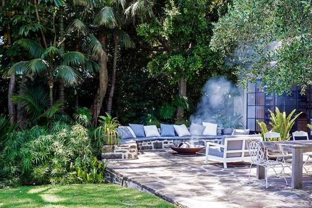 "This outdoor seating area, designed by [landscape gardener Daniel Baffsky](https://www.homestolove.com.au/a-sydney-harbourside-garden-by-daniel-baffsky-5984|target=""_blank"") is nestled among lush greenery, providing the perfect wind barrier. An open fire pit makes the space inviting even during the cooler months."