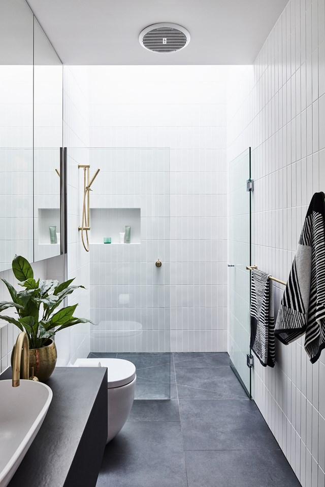 "A simple [monochrome palette](https://www.homestolove.com.au/monochrome-bathrooms-6390|target=""_blank"") is always a winner, and here we see it used to great effect. Brass tapware adds a point of difference, and please note the perfect placement of the heated towel rail."