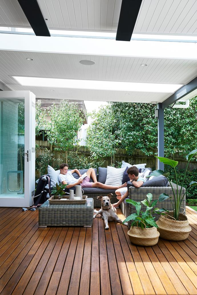 Tom (left) and Edward on their new and improved deck with rescue dog Topper, a red cattle x boxer. Sofa, chairs and coffee table, from Osmen Outdoor Furniture.