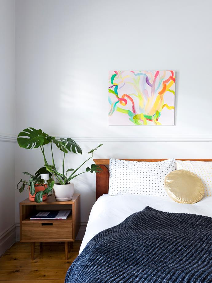 The master bedroom is simple and serene with hints of timber and pops of greenery.