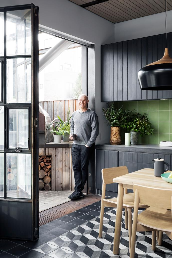 Architect Nick Harding on the threshold, next to the rear deck's Valoriani Forni pizza oven, which caters to the owner's frequent guests.