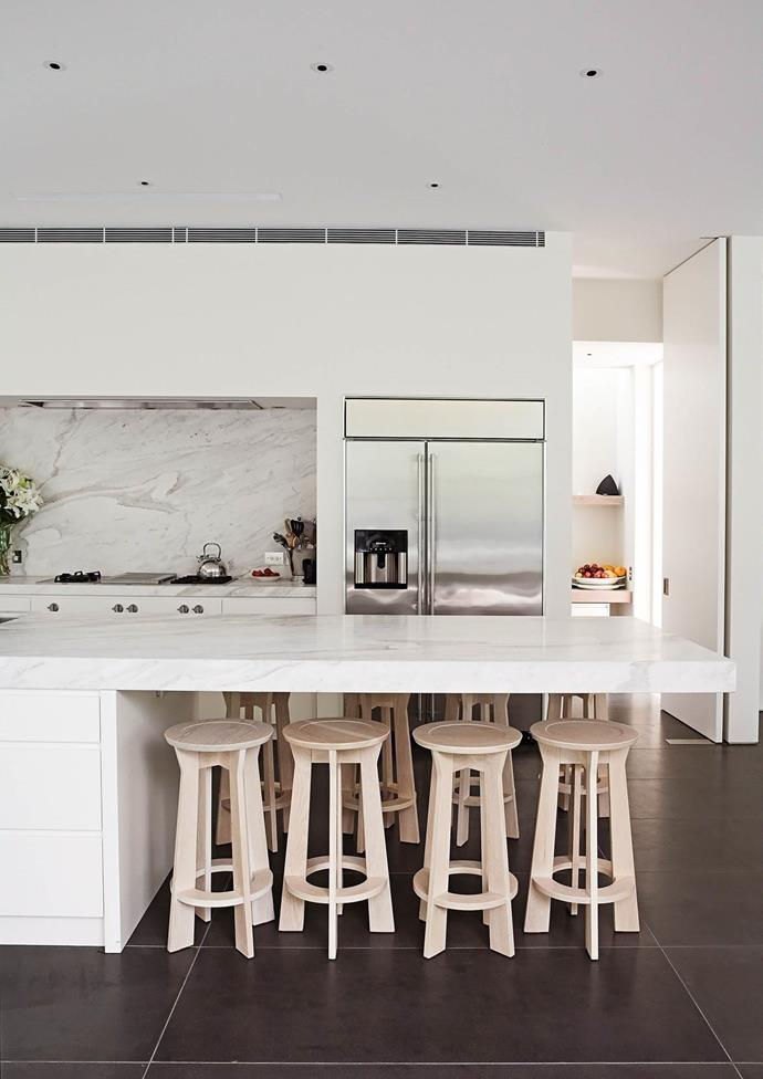 This owners of this kitchen opted for durable, and easy to clean, stone finish benchtops and splashbacks, so they could spend less time worrying about the mess and more time enjoying themselves. *Photo: Tim James / bauersyndication.com.au*