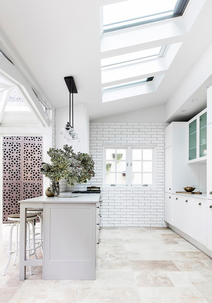 This classic white kitchen features a breakfast bar and an open plan layout that brings together the dining area and food prep space. *Photo: Maree Homer / Australian House & Garden*
