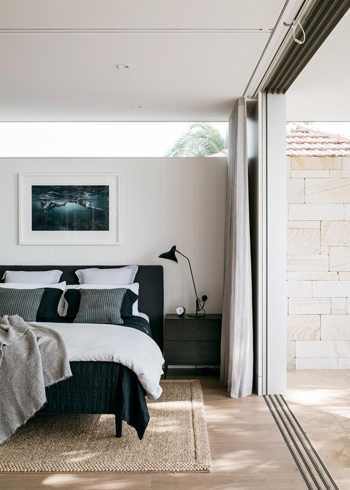In the main bedroom a work by Martine Emdur adds to the coastal vibe. The architects opened up the house with extensive floor-to-ceiling glass in the bedrooms and guest bathrooms.