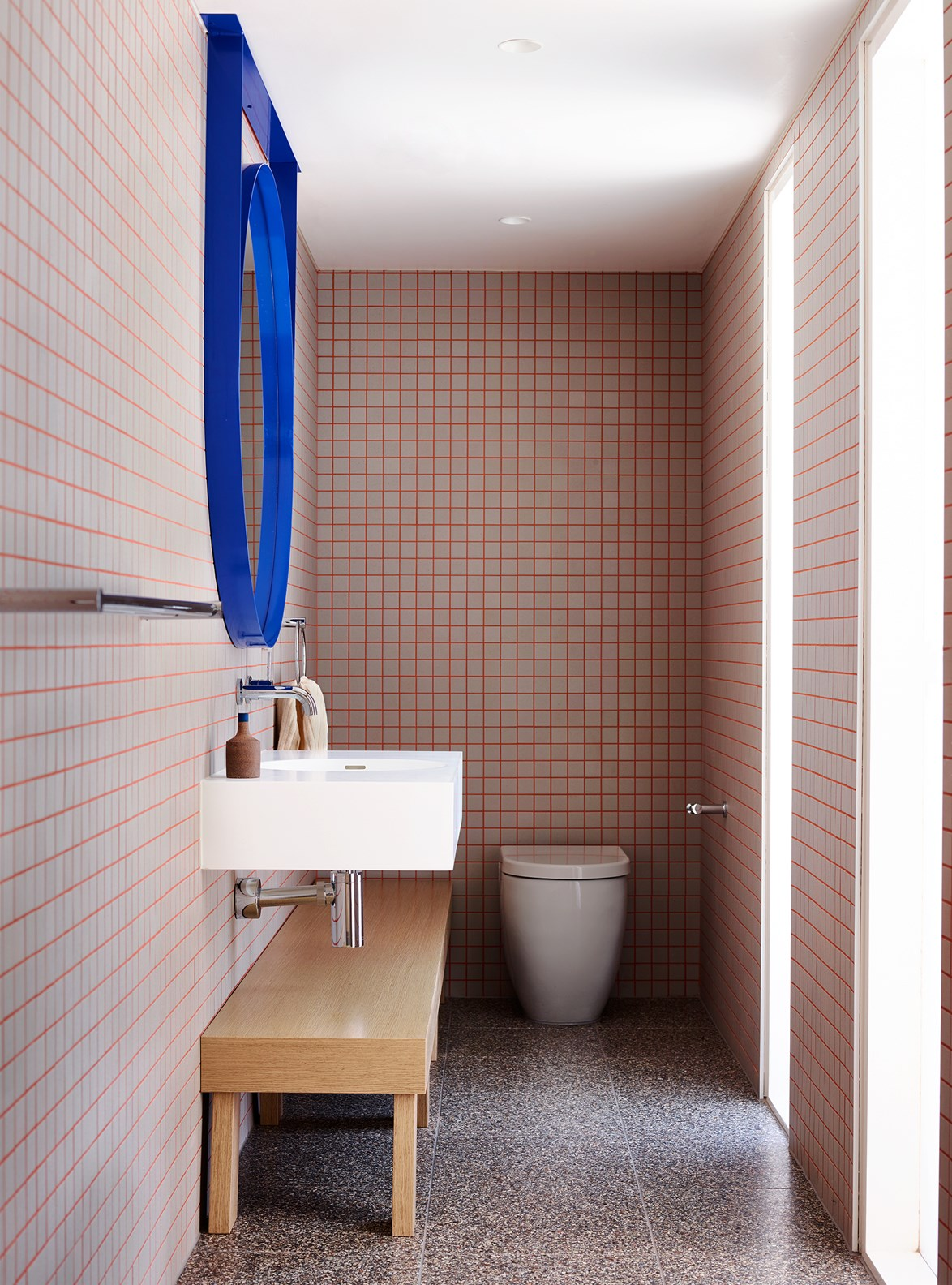 "Design-wise, [powder rooms](https://www.homestolove.com.au/8-bathrooms-with-a-hint-of-glamour-1-6024|target=""_blank"") are an opportunity to go wild. Pink grouting push the graphic aesthetic of this space to the limit while terrazzo flooring grounds the entire look. *Photo: Mark Roper / Story: Belle*"