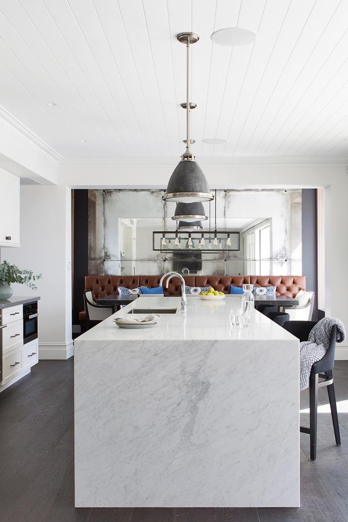 The Carrara marble bench and bright, white palette eases the transition to this modern extension, featuring an elegant timber-lined ceiling and handpainted cabinetry.